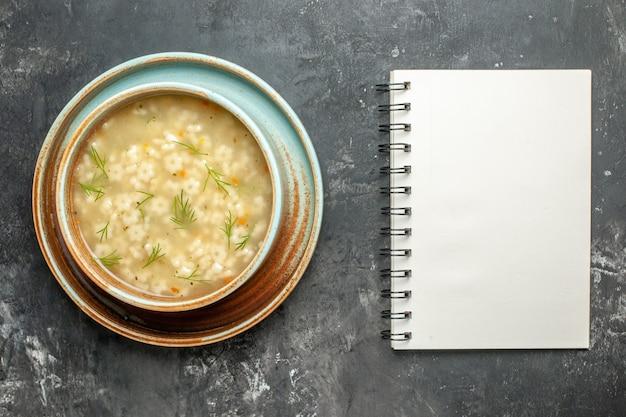 ボウルのトップビュースタースープ暗い背景のノートブック