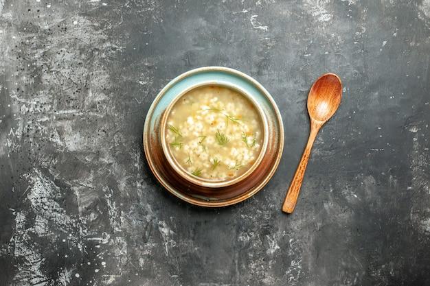 暗い背景のボウル木のスプーンでトップビュースタースープ