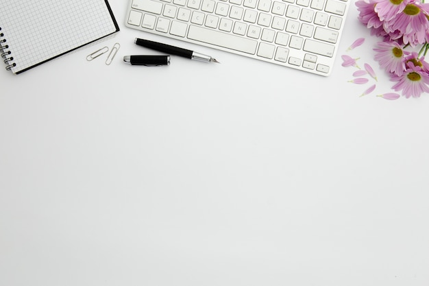 Top view stationary arrangement on desk with white keyboard