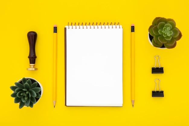 黄色の背景にトップビュー文房具配置