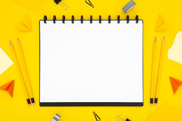 Top view stationery arrangement on yellow background with empty notebook