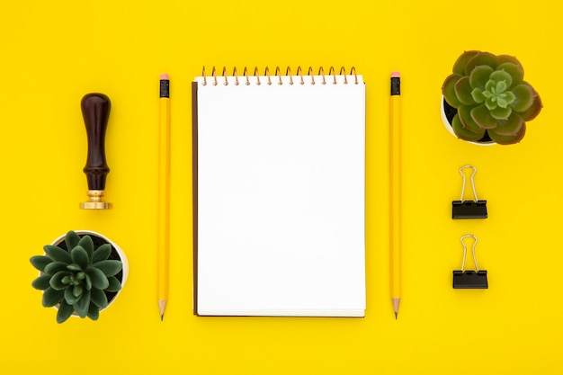 Top view stationery arrangement on yellow background