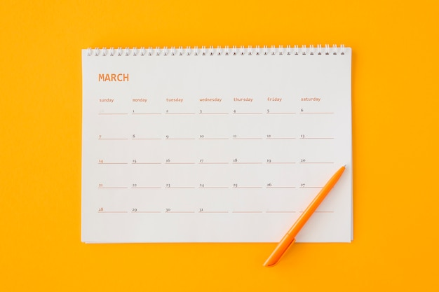 Top view stationery calendar with orange pencil