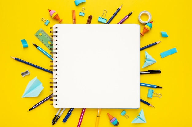 Top view stationery composition on yellow background