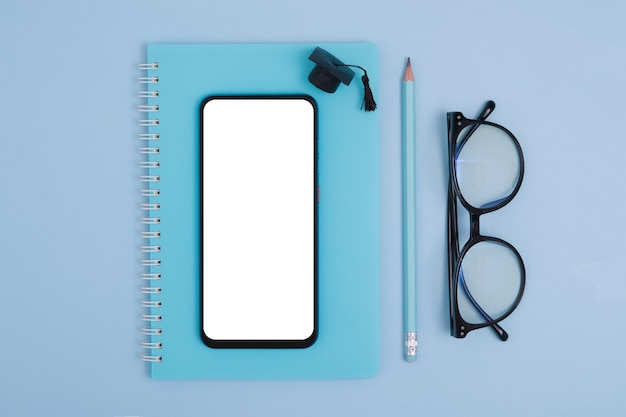 Top view of stationery, glasses with phone and graduate cap on blue surface