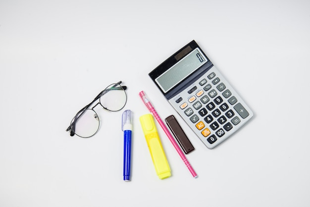Top view stationery have glasses one notebook and side calculator