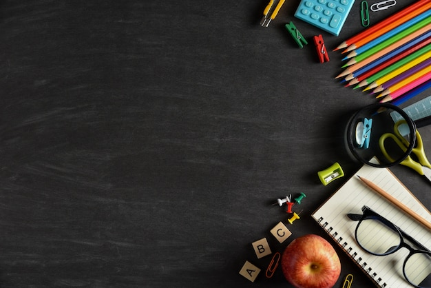 Top view of stationery or school supplies with books, color pencils, calculator, laptop, clips and red apple on chalkboard background.