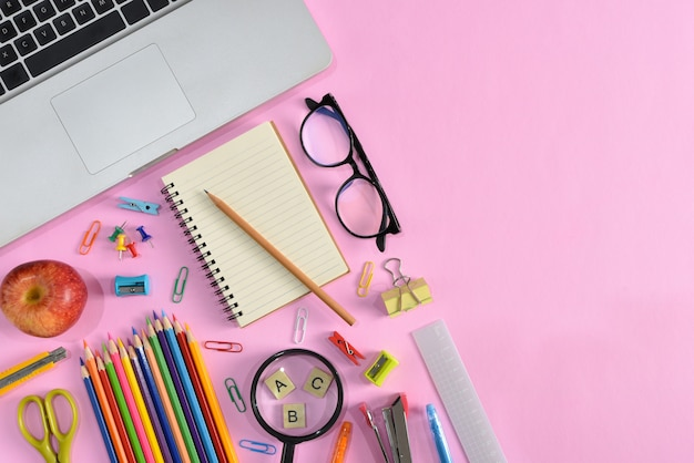 Top view of stationery or school supplies with books, color pencils, calculator, laptop, clips and red apple on pink background.