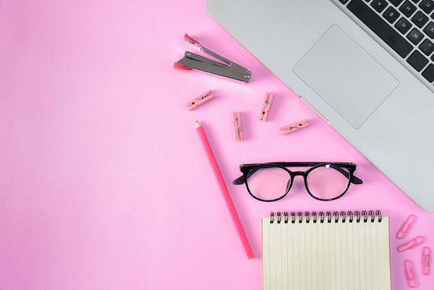 Top view of stationery or school supplies with books, color pencils, laptop, clips and glasses on pink background with copyspace. education or back to school concept.