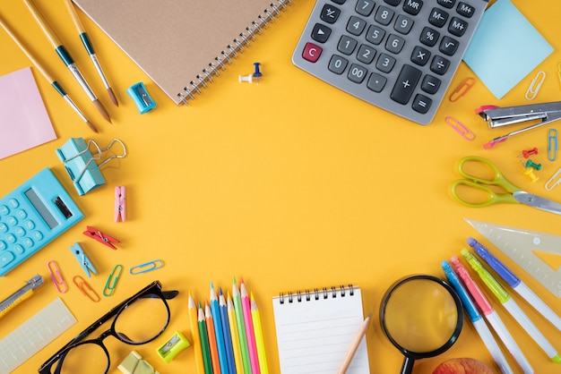 Top view of stationery or school supplies on yellow background
