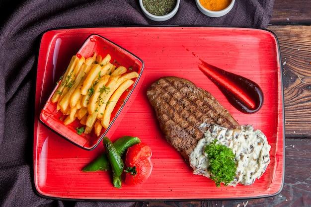 Вид сверху стейк с жареным картофельным соусом, специями на красной тарелке
