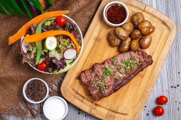 구운 감자와 야채 샐러드와 함께 상위 뷰 스테이크