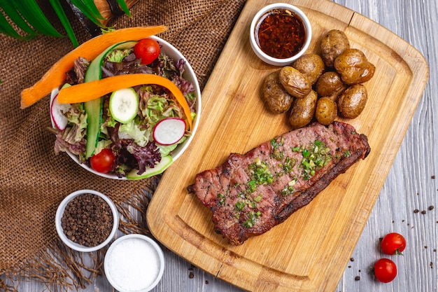 Top view steak with baked potatoes and vegetable salad