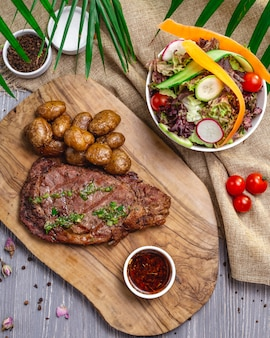 Top view steak with potatoes and sauce on the board with salad and vegetables