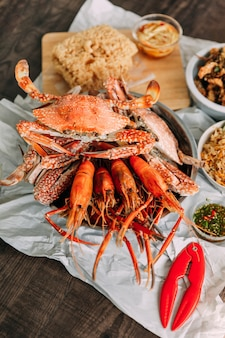 Top view of steamed flower crabs and grilled prawns (shrimps) with crab cracker on paper with other seafoods in background.