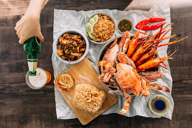 Top view of steamed giant mud crabs, grilled prawns (shrimps), crab fried rice, pepper and garlic soft-shell crab, crispy catfish, mango salad and thai spicy seafood sauce. served with beer.