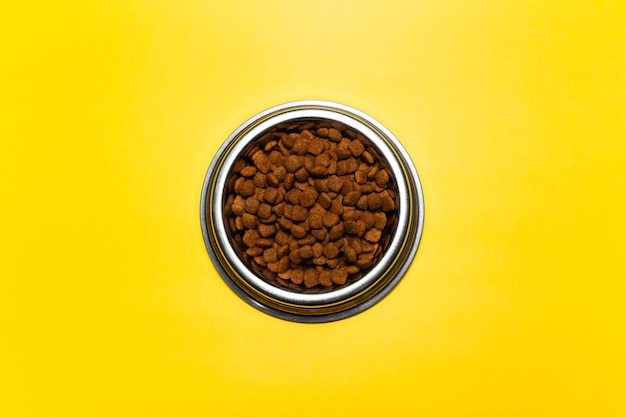 Top view of steel bowl with dry food for cats on background of yellow color.