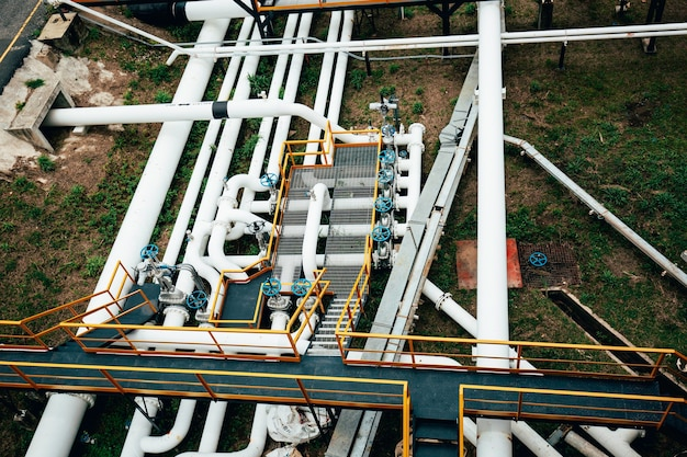 Top view steel long pipes and valves factory during refinery petrochemistry industry in gas and oil site distillery