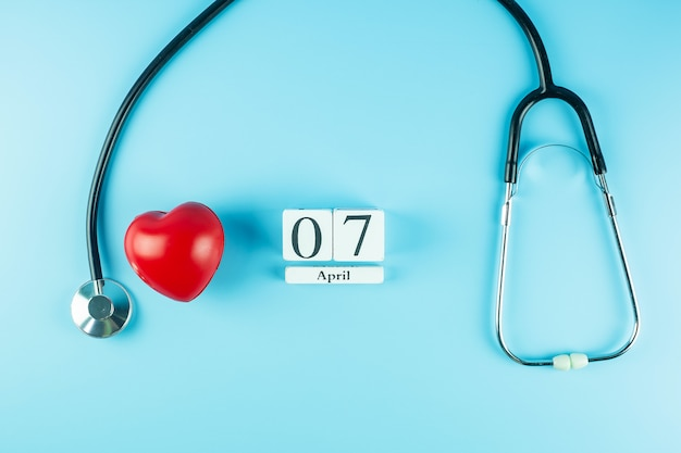 Top view stethoscope, red heart shape and 7th april calendar. world health day