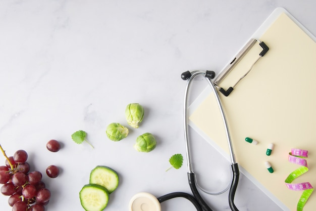 Top view stethoscope with cucumber slices and grapes