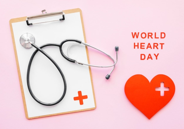 Top view of stethoscope with notepad and paper heart