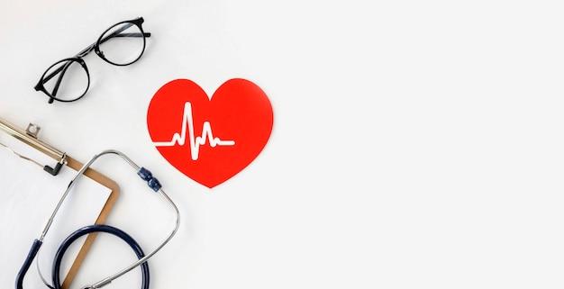 Vista dall'alto dello stetoscopio con cuore di carta e copia spazio