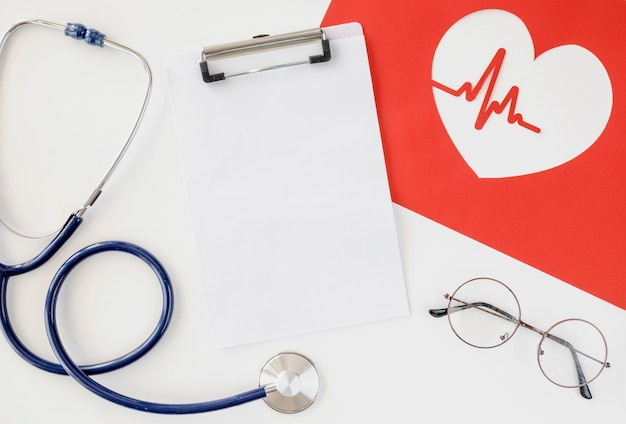 Vista dall'alto dello stetoscopio con cuore di carta e blocco note