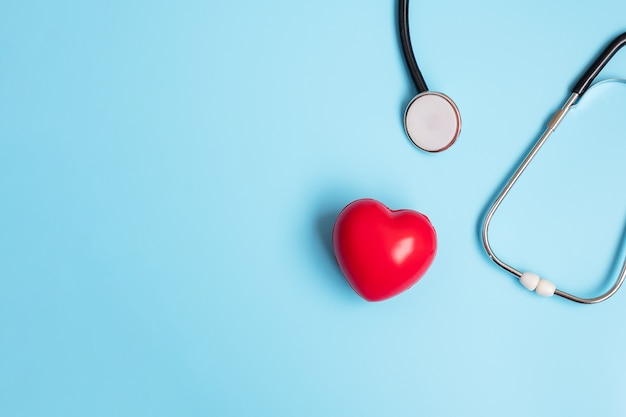 Top view stethoscope with red heart shape on blue background with copy space for text. healthcare, life insurance, health day, world heart day and happy doctor day concept