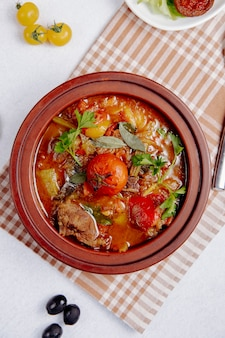 Top view of stewed meat with potatoes and tomatoes in a clay pot