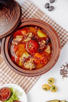 Vista dall'alto di carne in umido con pomodori e patate in una pentola di terracotta