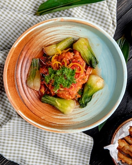 Top view of stewed vegetables in spicy tomato sauce in a plate on plaid fabric
