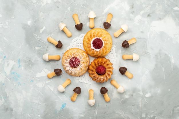 灰色の光の表面のケーキクッキービスケットにクリームケーキが並ぶ異なるチョコレートケープ付きソフトトップビュースティックビスケット