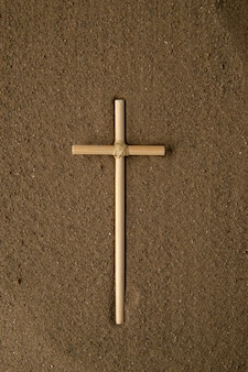 Top view of stick cross on brown sand