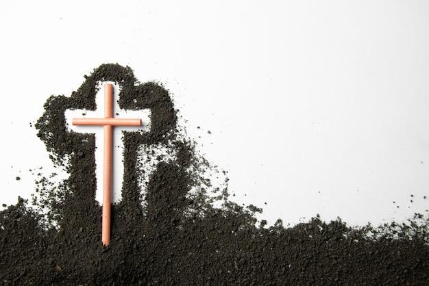 흰 벽에 어두운 흙과 십자가 상위 뷰 스틱