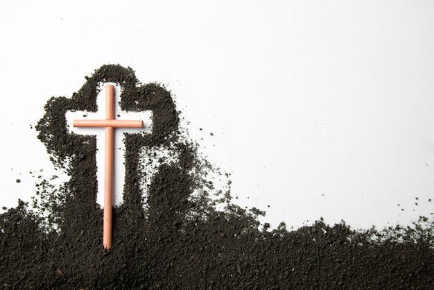 Top view stick cross with dark soil on a white wall