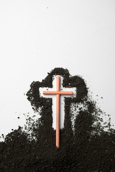 Top view stick cross with dark soil on white wall
