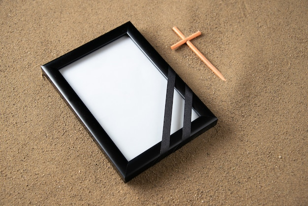 Top view of stick cross with picture frame on the sand