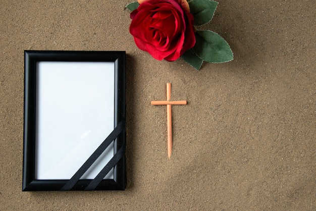Top view of stick cross with red flower and picture frame on the sand death funeral palestine