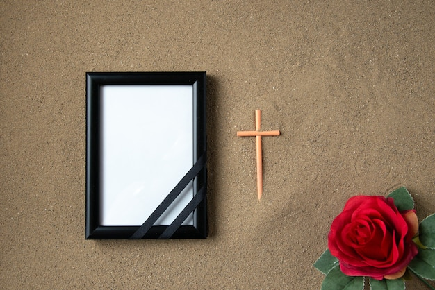 Top view of stick cross with red flower and picture frame on the sand death palestine