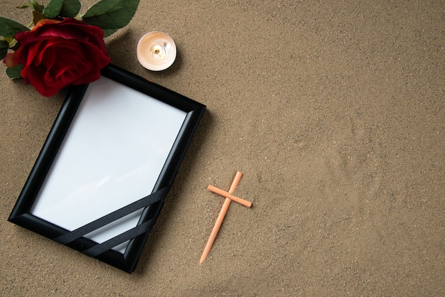 Top view of stick cross with red flower and picture frame on the sand