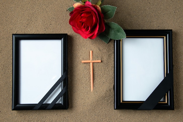 Top view of stick cross with red flower and picture frames on the sand