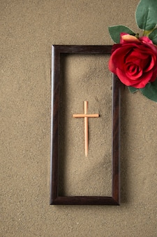 Top view of stick cross with red flower on the sand