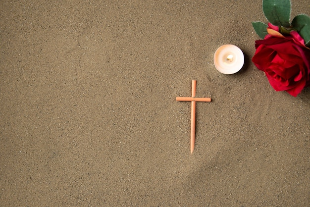 Top view of stick cross with red flowers on the sand