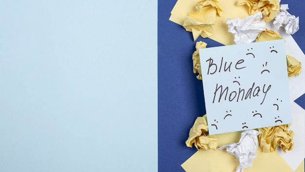 Top view of sticky note with frowns for blue monday