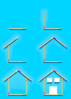 Top view of sticky notes and fluorescent marker pens forming a drawing of a house on pastel blue background.