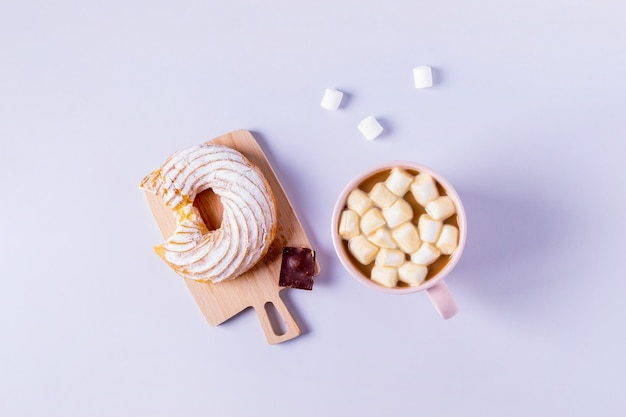 Top view of still life of a bitten cake on a small serving board and a cup of cocoa with marshmallows. selective focus, horizontal orientation.