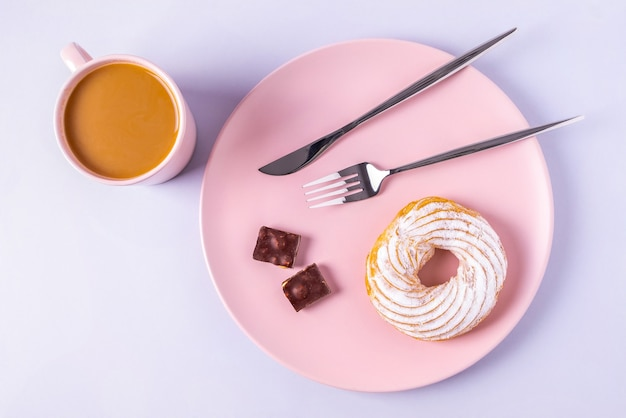 Top view still life of cake on a pink plate, cutlery and cups with cocoa or coffee with milk. selective focus, horizontal orientation.