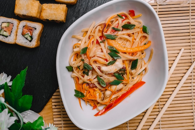 Top view stir-fried noodles with grilled chicken bell pepper and carrot with sushi roll on the table