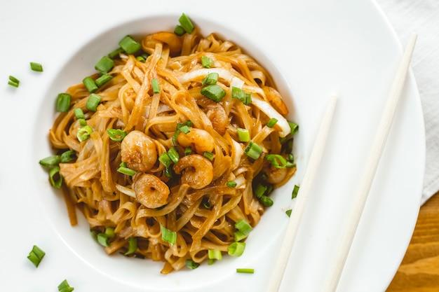 Vista dall'alto di noodles saltati in padella con salsa di soia di gamberi e cipollotti su un piatto