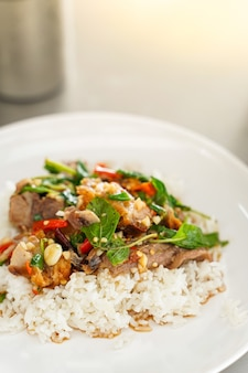 Top view, stir-fried thai basil with meat and basils sort in a white dish.